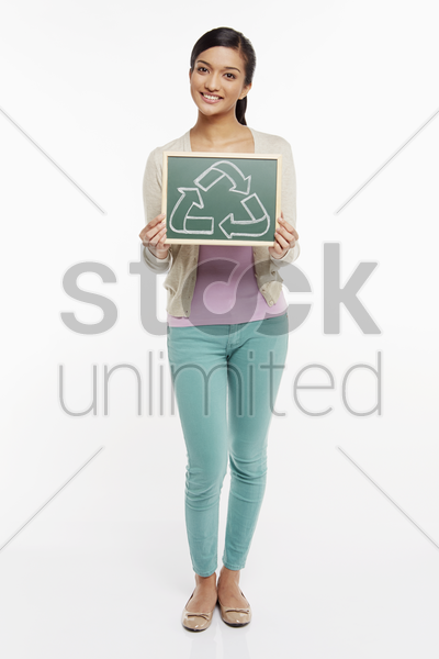 woman holding up a black board with a recycle symbol on it stock photo