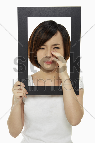 woman holding up a black picture frame, crying stock photo
