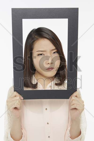 woman holding up a black picture frame, looking angry stock photo