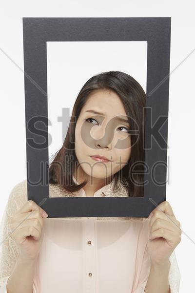 woman holding up a black picture frame, looking sad stock photo