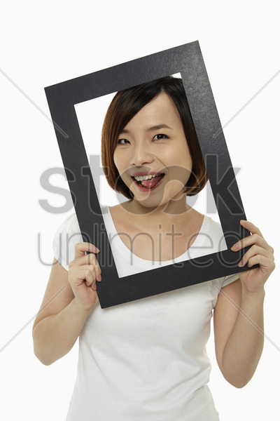woman holding up a black picture frame, sticking her tongue out stock photo