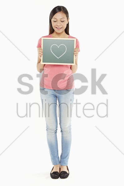woman holding up a blackboard with a heart shape doodle stock photo