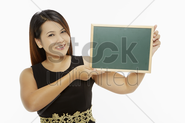 woman holding up a blank blackboard stock photo