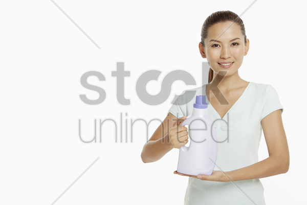 woman holding up a bottle of detergent stock photo