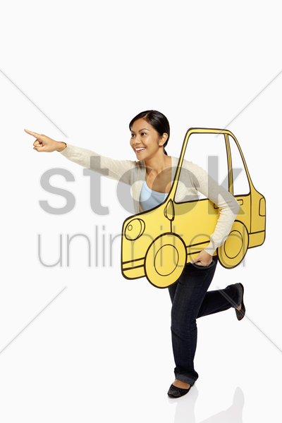 woman holding up a cardboard car, pointing forward stock photo
