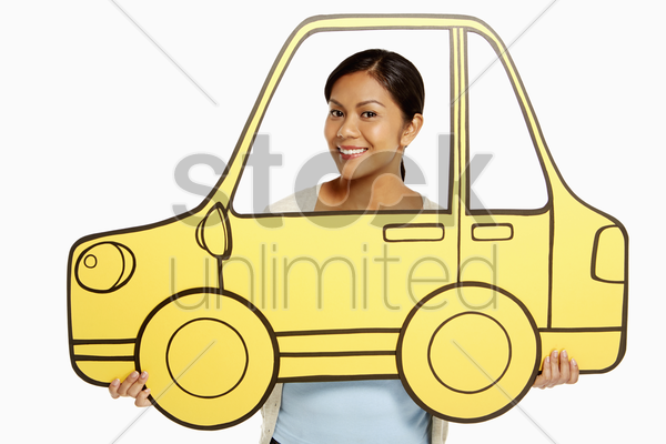 woman holding up a cardboard car stock photo