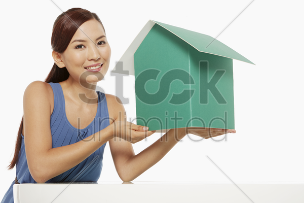 woman holding up a cardboard house stock photo