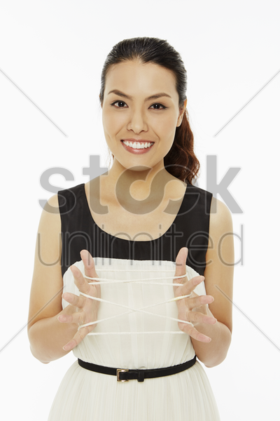 woman holding up a cat's cradle stock photo