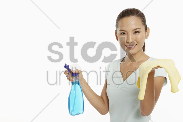 woman holding up a cloth and a spray bottle stock photo