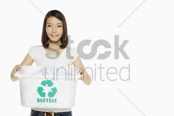 woman holding up a container of shredded paper stock photo