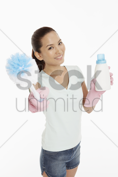 woman holding up a detergent bottle and a brush stock photo