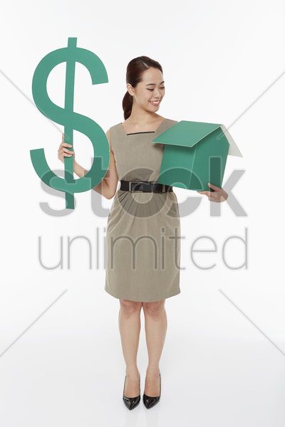 woman holding up a dollar sign and a house stock photo