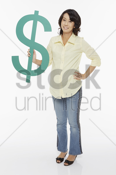 woman holding up a dollar sign stock photo