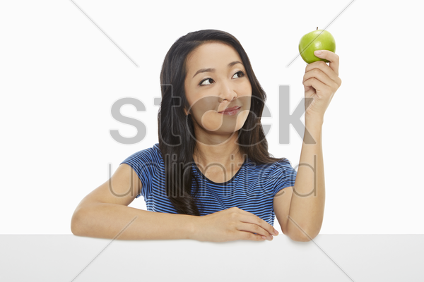 woman holding up a green apple stock photo