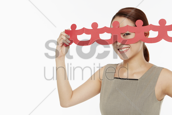 woman holding up a human paper chain stock photo