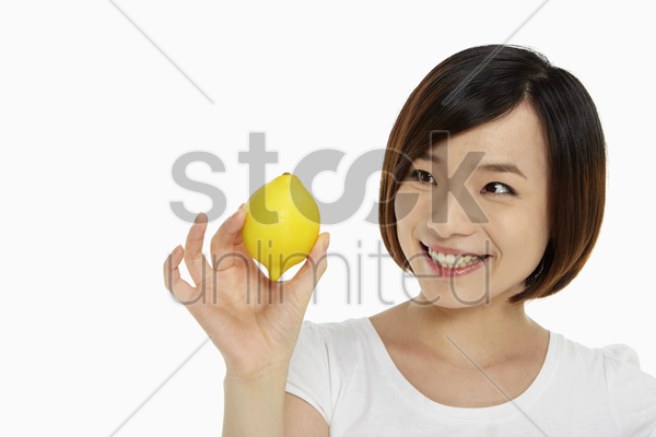 woman holding up a lemon stock photo