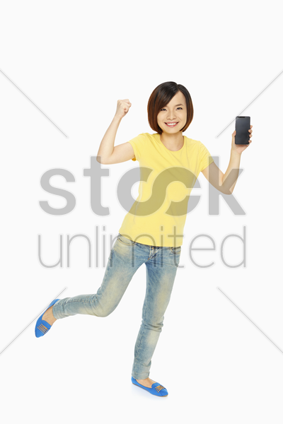 woman holding up a mobile phone and cheering stock photo