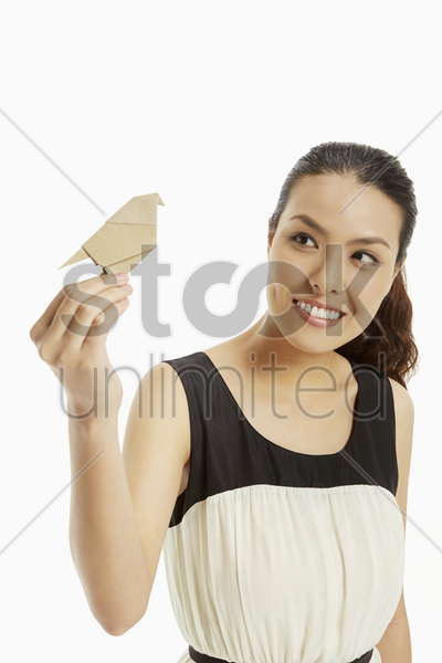 woman holding up a paper bird stock photo