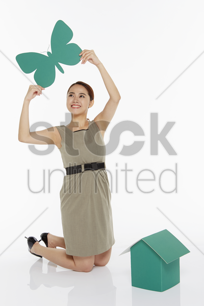 woman holding up a paper butterfly stock photo