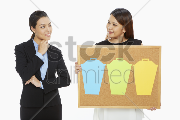 woman holding up a pin board while the other contemplates stock photo