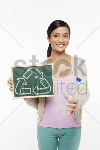 woman holding up a plastic bottle and a black board stock photo