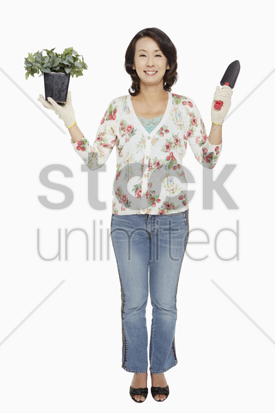 woman holding up a potted plant and a spade stock photo