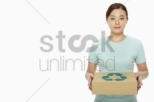 woman holding up a recyclable box stock photo