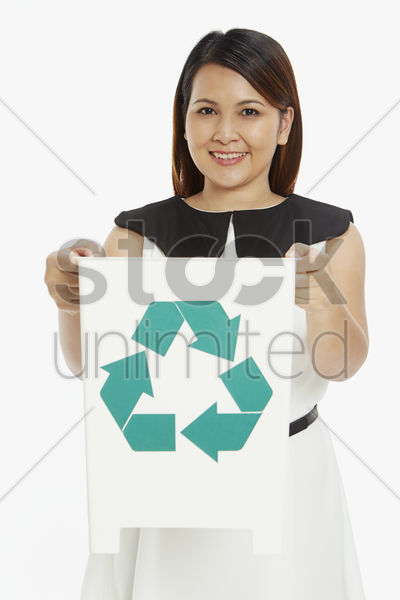 woman holding up a recycle bin stock photo