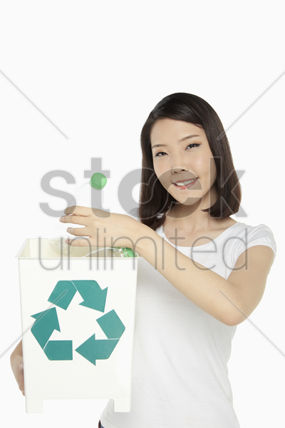 woman holding up a recycling bin filled with plastic bottles stock photo