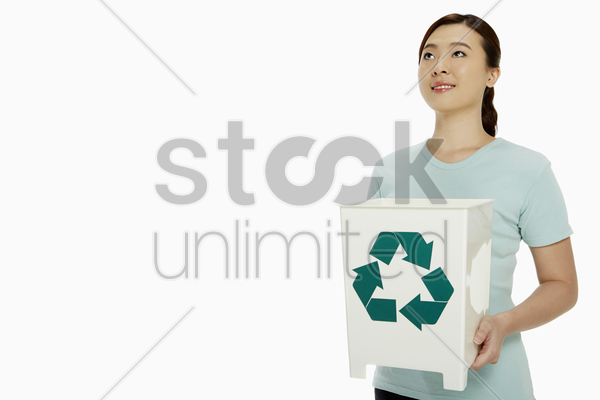 woman holding up a recycling bin stock photo