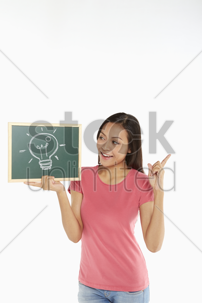 woman holding up a small blackboard with a light bulb doodle stock photo