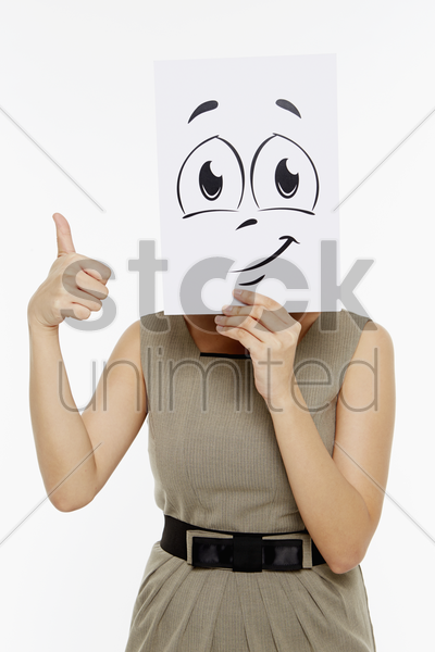 woman holding up a smiley face doodle stock photo