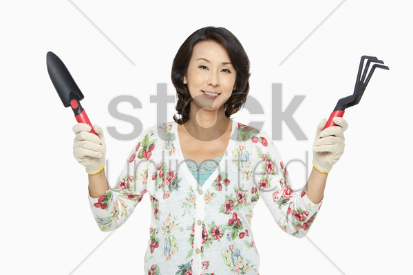 woman holding up a spade and a garden fork stock photo