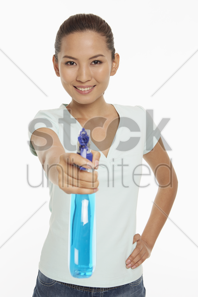 woman holding up a spray bottle stock photo