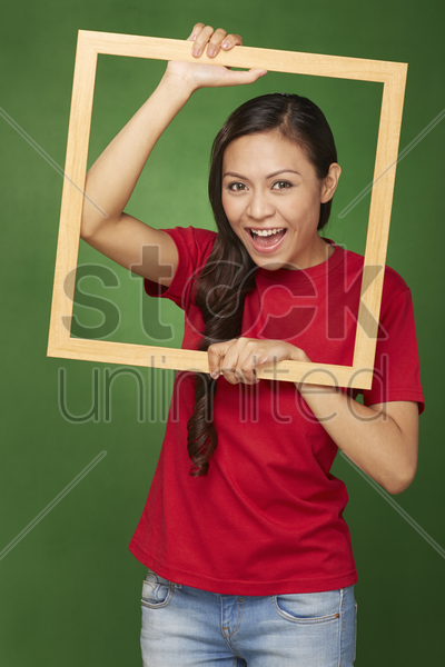 woman holding up a wooden frame, smiling stock photo