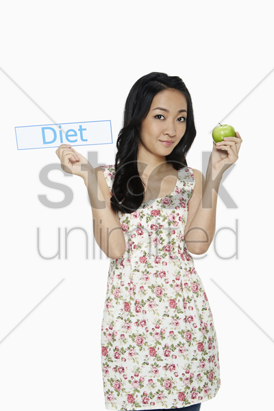 woman holding up an apple and a small placard stock photo