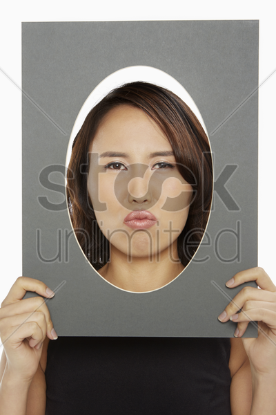 woman holding up an oval frame stock photo