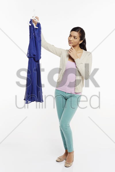 woman holding up and looking at a blue dress stock photo