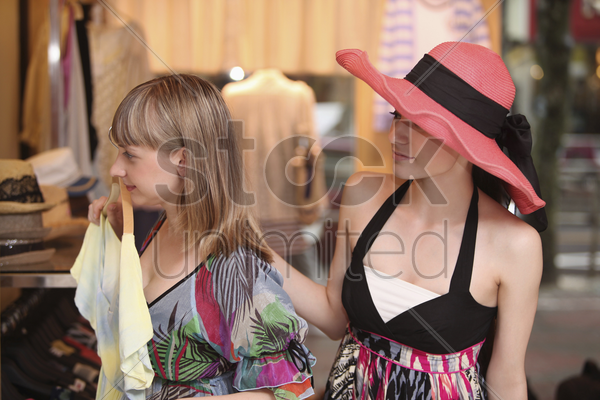 woman holding up blouse in front of mirror, her friend behind her stock photo