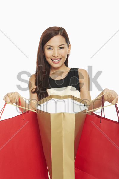 woman holding up her shopping bags stock photo