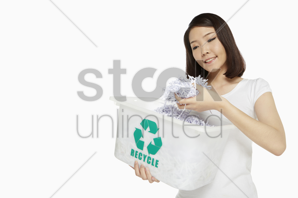 woman holding up pieces of shredded paper stock photo