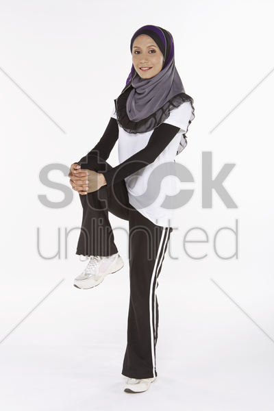 woman holding up right leg stock photo