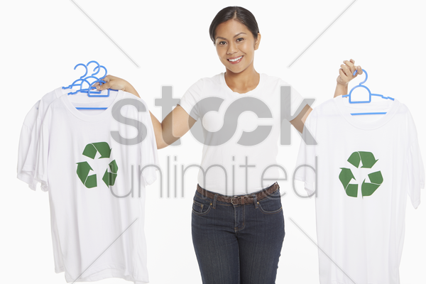woman holding up t-shirts with a recycle logo on it stock photo