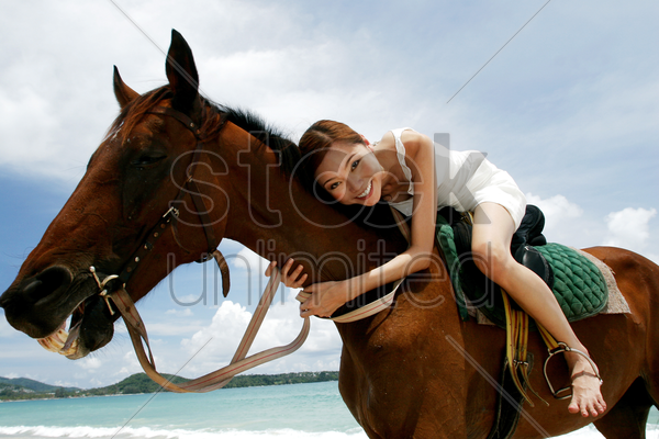 woman horse riding on the beach stock photo