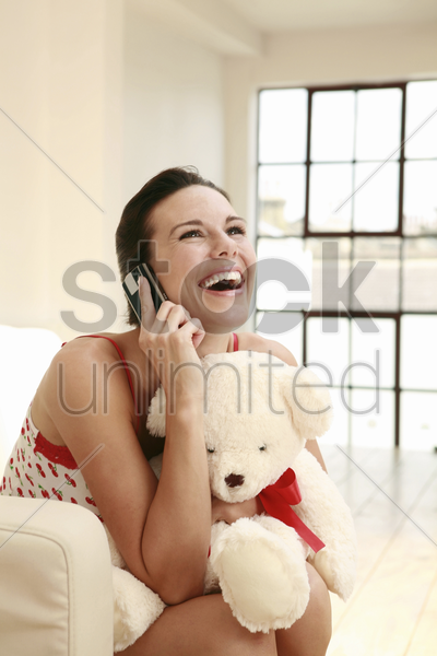 woman hugging a soft toy while talking on the mobile phone stock photo