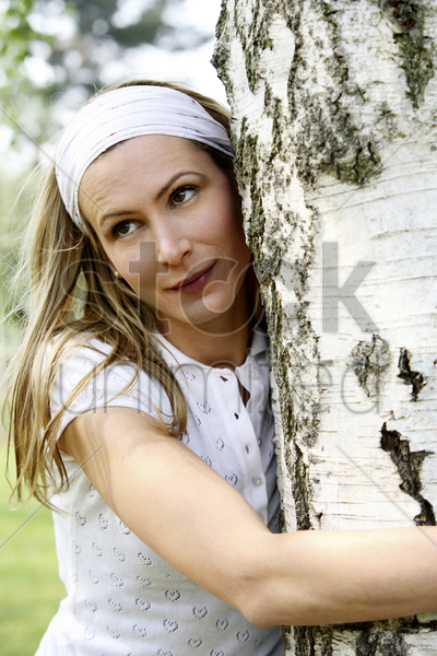 woman hugging a tree in the park stock photo