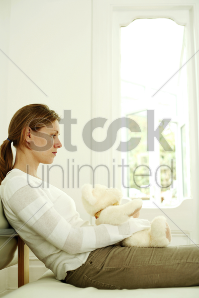 woman hugging teddy bear while daydreaming stock photo