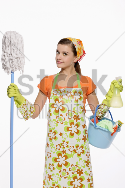 woman in apron holding mop and a pail of cleaning products stock photo