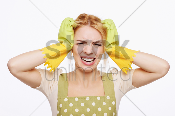 woman in apron looking frustrated stock photo