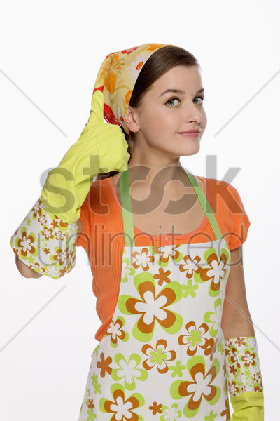woman in apron showing hands with rubber gloves on stock photo